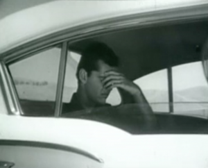 Johnny (Jack Nicholson) holds his head in the back of a car.