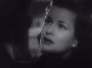 Evelyn (Joan Bennett) stares with concern, her lips parted.
