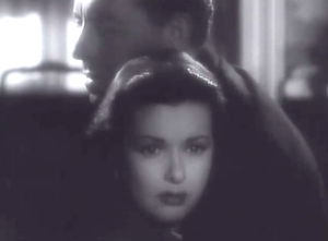 Johnny's (Paul Henreid) face is turned to the side as he holds Evelyn (Joan Bennett), whose face is turned forward. Both are sad.