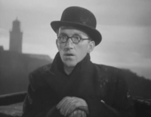 Wearing a dark coat, gloves, bowler hat and round glasses, Arthur (Arthur Askey) stares with his mouth open while a dimmed lighthouse looms behind him.
