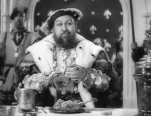In full regalia, bearded, corpulent Henry VIII (Charles Laughton) munches on a poultry leg with a smirk.