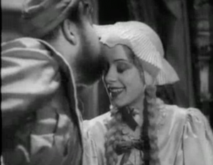 Both in bedclothes, Henry (Charles Laughton) kisses the forehead of a smiling Anne of Cleves (Elsa Lanchester).