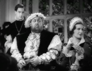 A greying Henry (Charles Laughton) sits at an event with Katherine (Binnie Barnes) as Culpeper (Robert Donat) looks on behind them.