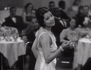In a silky white dress, Ethel (Lena Horne) looks over her shoulder as she sings on the empty dance floor of a posh nightclub, watched by elegantly dressed Black patrons.
