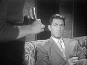 Sitting on a sofa with a drink in his hand, Duke (Jock Mahoney) looks up at Lois (Elaine Edwards), shown from the midriff down and also holding a drink.