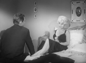 With platinum blonde hair and in a low-cut gown hiked up to the knee, Helen (Greta Thyssen) talks with Duke (Jock Mahoney), who sits at her feet in his suit.