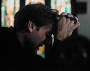 Shown in profile with stained glass windows behind him, Reverend Lohman (James Cromwell) sobs as he leans his forehead onto his folded hands.