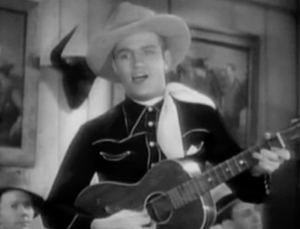 Wearing a light-coloured cowboy hat and a white bandana around his neck, Gene Autry plays guitar and sings in a saloon.