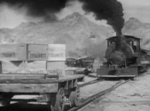 A train speeds toward a wagon laden with crates of dynamite.