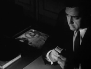 Viewed from slightly above and lit only by a desk lamp, Craig (Raymond Burr) speaks as he holds a microphone connected to a turning reel-to-reel tape recorder.