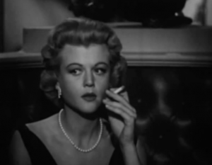 Sitting in a restaurant booth, blonde Myra (Angela Lansbury) wears a black dress and pearls as she holds a cigarette close to her mouth and looks to the side.