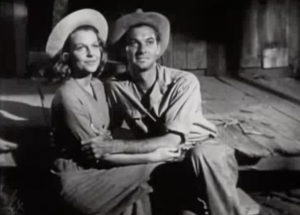 Sam (Zachary Scott) and Nona (Betty Field) sit on the front step of their new shack, holding each other and looking up.
