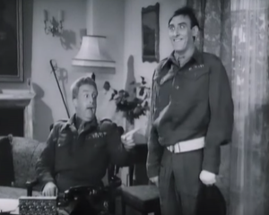 Both in military uniform, Private Eccles (Spike Milligan) smiles giddily as Colonel Bloodnok (Peter Sellers) talks and points from his desk.