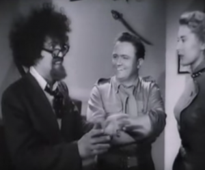 With wild dark hair, glasses and a goatee, Professor Purehart (Michael Bentine) talks animatedly to Harry (Harry Seacombe) and Carole (Carole Carr).