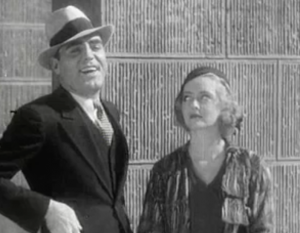 As Matt (Pat O'Brien) smiles broadly to someone across the street, Peggy (Bette Davis) gives him the side-eye.