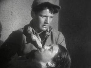 Jimmy (Junior Durkin) stares ahead as he holds an ailing Shorty (Junior Coghlan), who struggles to speak.