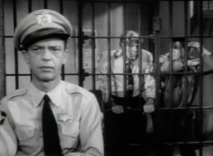 In the foreground, Barney Fife (Don Knotts) overhears convicts Doc and Tiny (Jack Lambert, Billy Halop) in the cell behind him.
