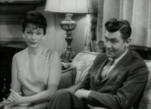 Sitting on a couch together, Helen (Aneta Corsaut) and Andy (Andy Griffith) smile expectantly at Barney.