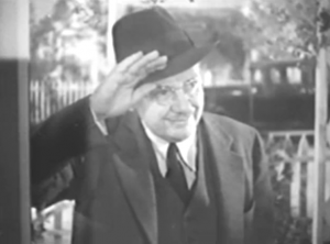 Wearing a hat, suit and round glasses, Doctor Christian (Jean Hersholt) raises his hand to peer through a screen door with a smile.