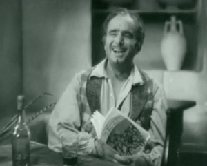 With thinning hair, a thin moustache and goatee and dressed casually, Don Juan (Douglas Fairbanks) laughs while holding a copy of The Private Life of Don Juan.