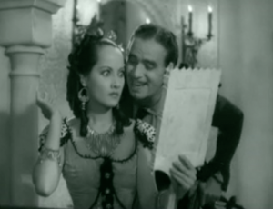 Antonita's (Merle Oberon) eyes go wide when she sees Don Juan (Douglas Fairbanks) smiling in her hand mirror.