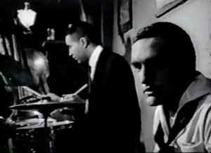 Wearing his white sailor's uniform, Johnny (Dennis Hopper) sits almost beside a jazz drummer playing in a club.