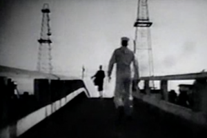 Johnny (Dennis Hopper), in his white sailor's uniform, follows a woman in black across a footbridge between oil rig towers.