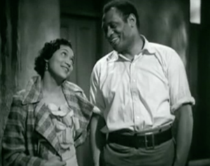 In an apartment hallway, Manda (Elisabeth Welch) and Joe (Paul Robeson) smile at each other.