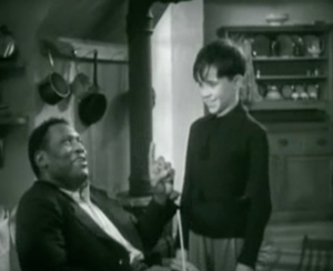 Young Gerald (Eldon Grant) smiles as Joe (Paul Robeson) sits holding a finger up to him.