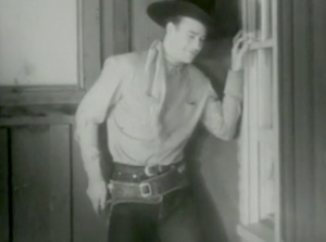 John (John Wayne) smirks as stands outside an open window, overhearing the discussion inside.