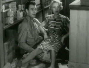After falling, Anne (Mary Kornman) sits on John's (John Wayne) lap on the floor behind her store counter.