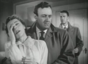 Ed (Lee J. Cobb) holds Lois (Jane Wyatt) as she pretends to be faint, while Andy (John Dall) stands at a distance behind them.
