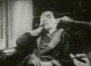 With a smoking jacket over his suit, Holmes (Raymond Massey) lounges on the couch with his hand over one eye and peering to the side with the other eye and a cocked brow.