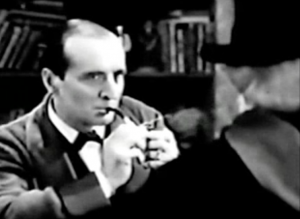 Holmes (Arthur Wontner) lights his pipe as he watches a disguised Moriarty (Norman McKinnell), who faces him.