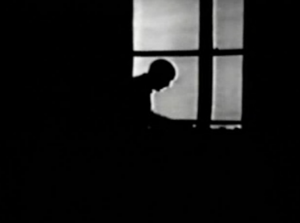 The profile of Sherlock Holmes (Arthur Wontner) is silhouetted in a window at night.