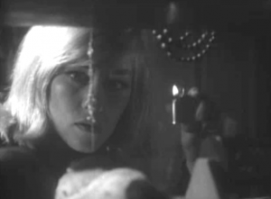 Holding a lit cigarette lighter, Louise (Luana Anders) looks through a cluttered shelf in a child's room, a bracelet hanging down and splitting the view of her face.