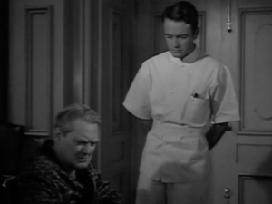 In his white smock, Kildare (Lew Ayres) looks down at Gillespie (Lionel Barrymore) wearing a robe, sitting in his chair, turned away bitterly.