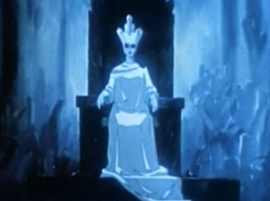 In white robes and headdress, The Snow Queen sits on a throne in her palace of ice.