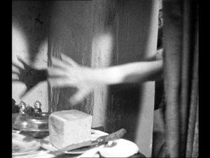 A blurred hand reaches out from behind a curtain, above some bread and a large knife on a side table.
