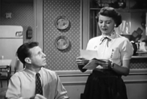 Sitting at a table, Ozzie Nelson looks up at his wife Harriet as she reads some mail.