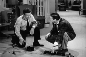 Wearing button-down shirts and ties, Ozzie (Ozzie Nelson) and Thorny (Don DeFore) crouch on the Ozzie's living room floor with a train set.