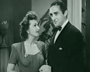 In the new club, Judy (Rosemary Lane) looks admiringly at Mickey (Sheldon Leonard).