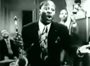 Holding his saxophone, Louis Jordan sings with his band playing behind him.