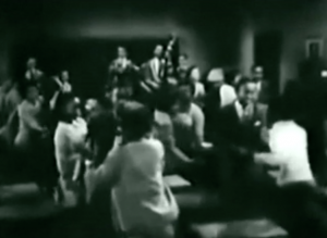 Students dance among the desks of a classroom while Louis' band plays up front.