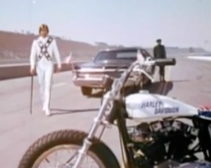 Using a black cane and wearing a white jumpsuit with a blue X with white stars across his chest, Evel Knievel (George Hamilton) walks from a limousine to his Harley-Davidson motorcycle.