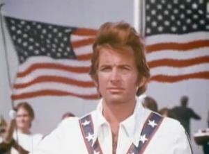 In his red, white and blue jumpsuit, Evel (George Hamilton) stands with two American flags flying behind him.