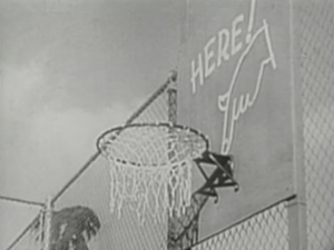 "The backboard of a basket has artwork of a hand pointing down at the hoop with the word ""Here!"""