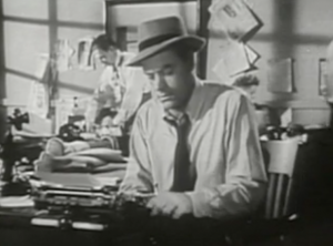 Wearing a hat, shirt and tie, Pete (John Ireland) sits typing at a typewriter in a newsroom.