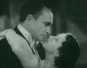 In profile, Karl (Conrad Veidt) and Madeleine (Vivien Leigh) gaze at each other with her arms around him.