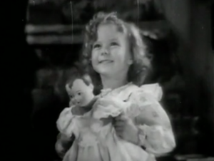 With her curly blonde hair, little Mary (Shirley Temple) smiles as she holds a doll.